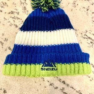 Snowy, Blue/Green/White beanie with poof on top.